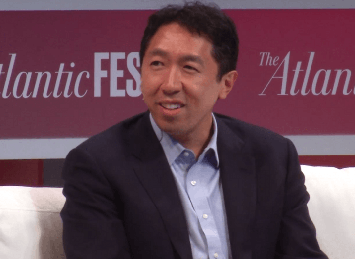Andrew Ng in a black blazer and blue shirt sitting on stage at an event.