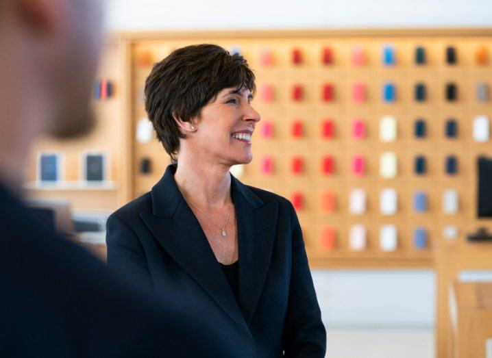 Woman with short black hair and dark blue suit standing smiling in an Apple Store.