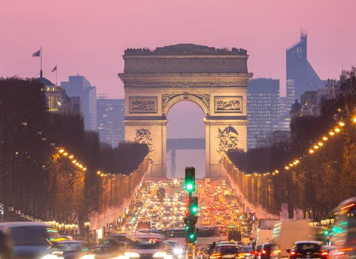 The Champs-Elysees lined with traffic with the Arc de Triomphe at the end against a pink sunset sky.