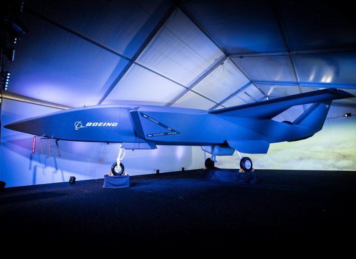The angular Boeing Airpower Teaming System lit up by spotlights at its unveiling against a blue and white background.
