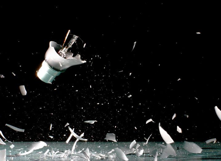 A smart lighbulb smashing to pieces against a black background.