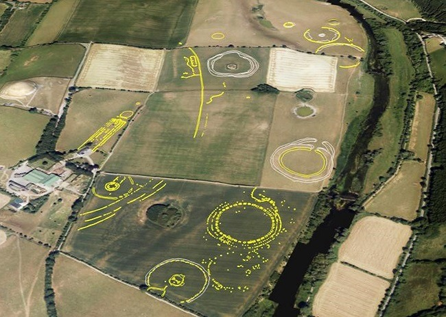 Aerial photo of buried circular structures represented by digitally enhanced yellow and white colours.