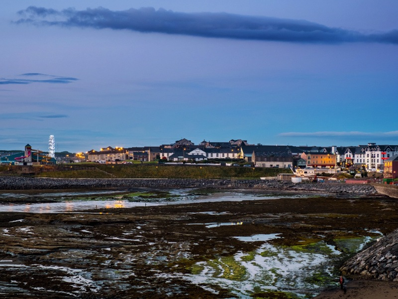 A view of the tourist town of Bundoran in Donegal showing the lights and hotels from a distance.