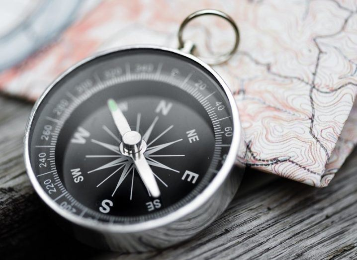 Silver compass pointing north, leaning against a map on a grey wooden table.