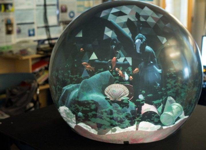 The crystal ball-shaped display in a lab shown projecting an underwater scene.
