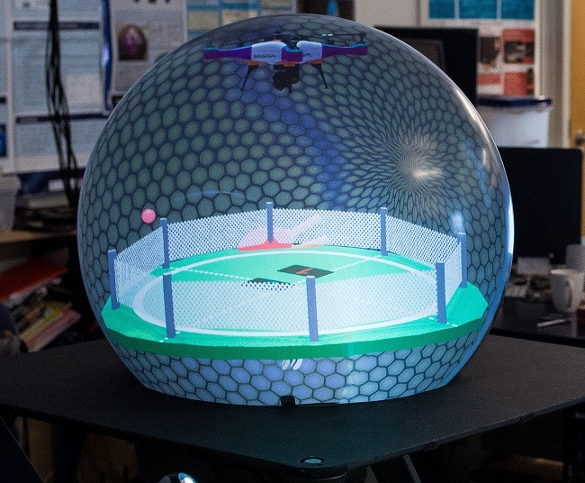 The crystal ball shaped display in the lab with a soccer pitch projection inside.