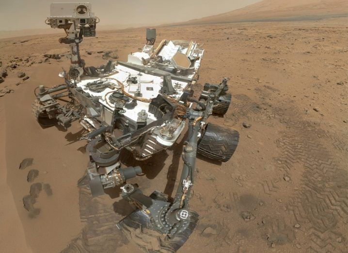Selfie of the Curiosity Rover with a desert-like Martian expanse in the background.