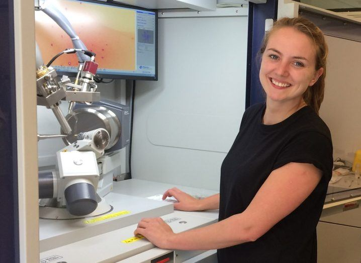 Young smiling woman in a black top smiling in front of lab equipment.