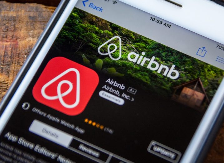 Airbnb app installation screen on an Apple iPhone, featuring the company logo.