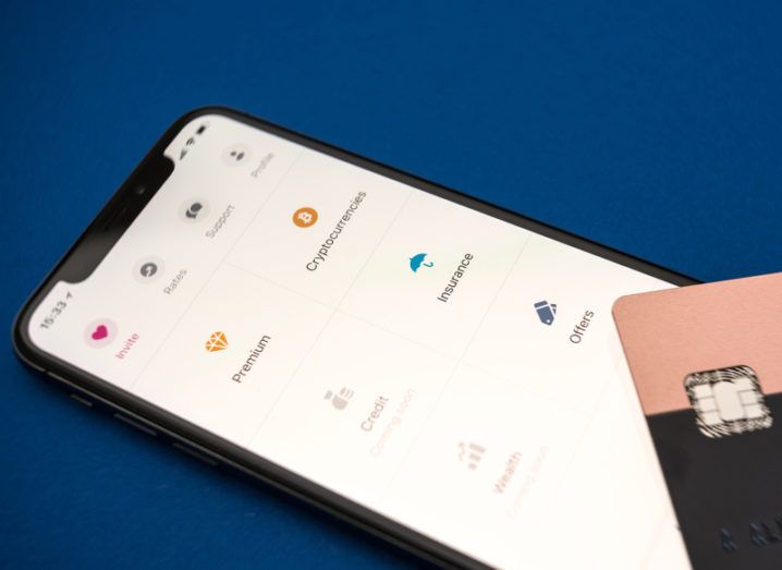 A smartphone screen displays options from the Revolut app menu including 'Cryptocurrencies' and 'Insurance'. A Revolut credit card is placed on top of the phone.