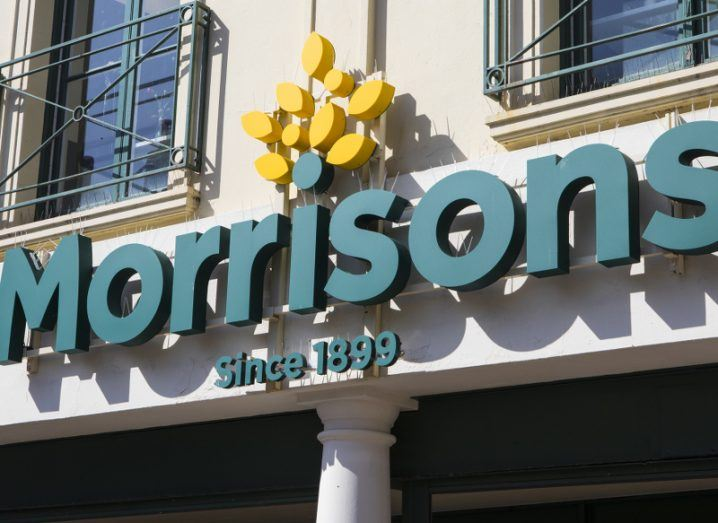 The green text and yellow flowering details of a Morrisons logo on the front of a building, beneath two windows.