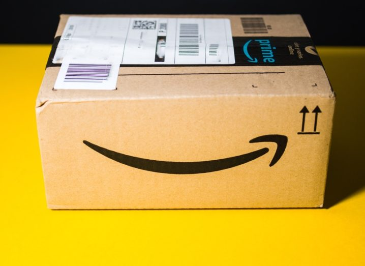 Small Amazon cardboard delivery box sitting on a bright yellow surface.