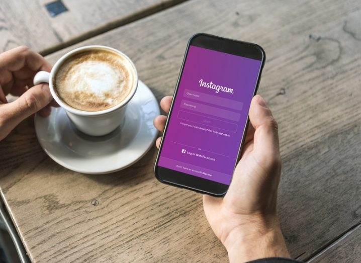 A man holding a mobile phone with the Instagram login screen open, a cup of coffee on a table in the background.