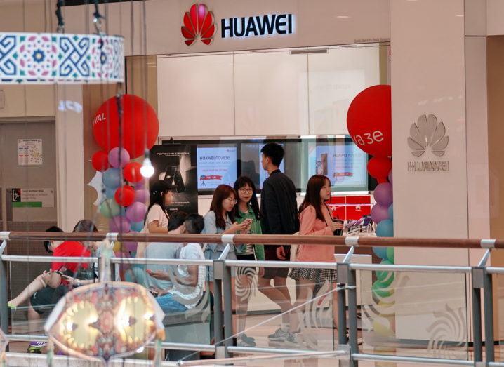 Shoppers walking past a Huawei retail store in Kuala Lumpur, Malaysia.