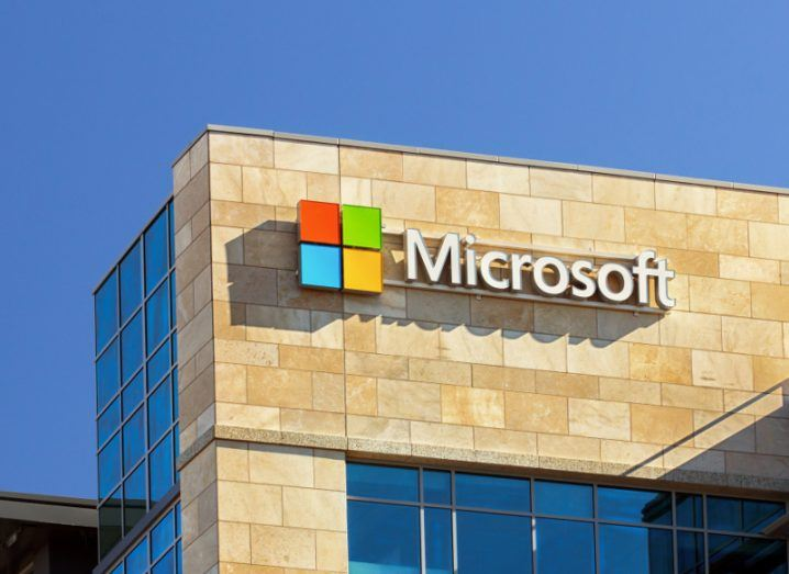 A view of a sand-coloured building emblazoned with the Microsoft logo on a bright and cloudless day.