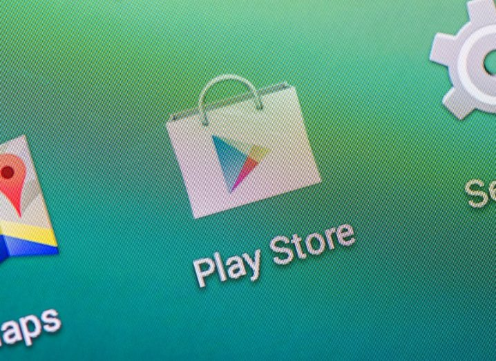Google Play Store app icon, a triangular play button, on a smartphone with green background.