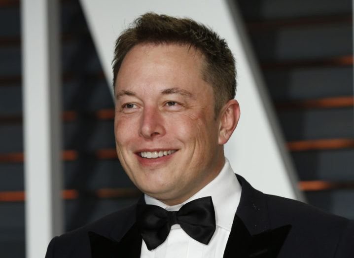 Elon Musk smiling off to the distance while wearing a black tuxedo, white shirt and bow tie.
