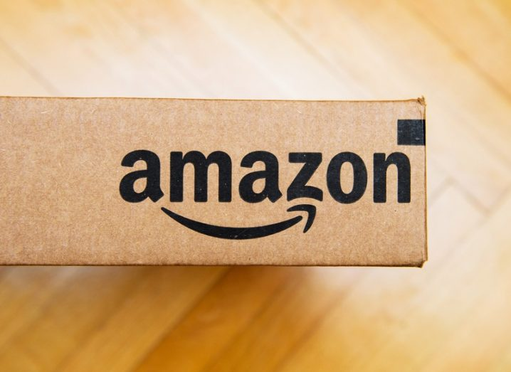 Amazon logo printed on a cardboard package, which is sitting on a parquet wood floor.