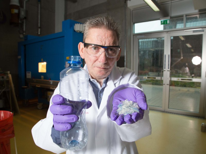 Middle-aged male researcher in white lab coat and purple gloves holds up a plastic bottle in one hand and in the other a composite raw material that can be used to make car and tractor parts.