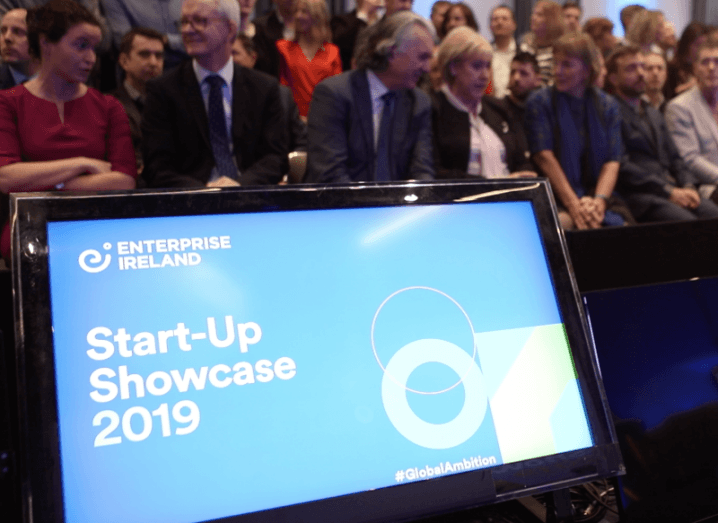 A large group of people sitting behind a blue screen that says Start-up Showcase 2019.