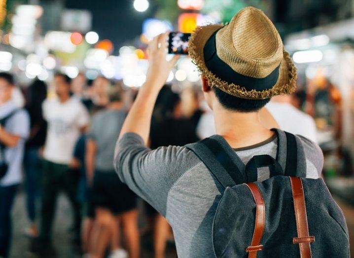 Man wearing a straw hat taking a photo on a busy street while on holiday.
