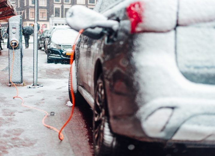 An EV parked on the side of a road covered in snow at a public charging point.