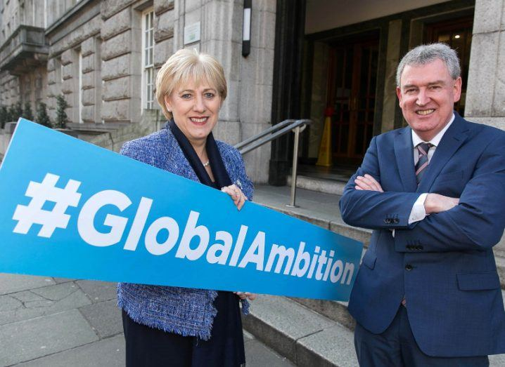 Man and woman in suits standing with a blue sign that reads global ambition.