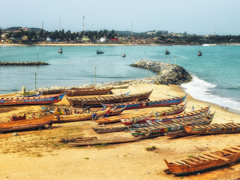 Boats on a beach at Cape Coast, Ghana, with cell towers visible in the distance.