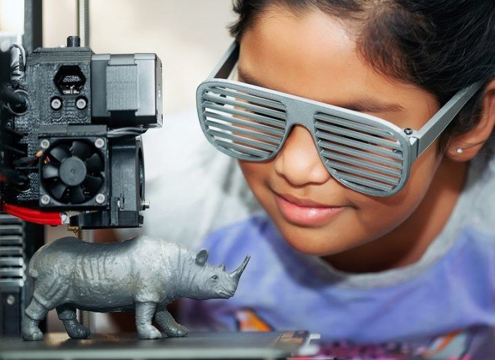 Girl wearing 3D-printed glasses with grill looking at a 3D printer making a small rhino.