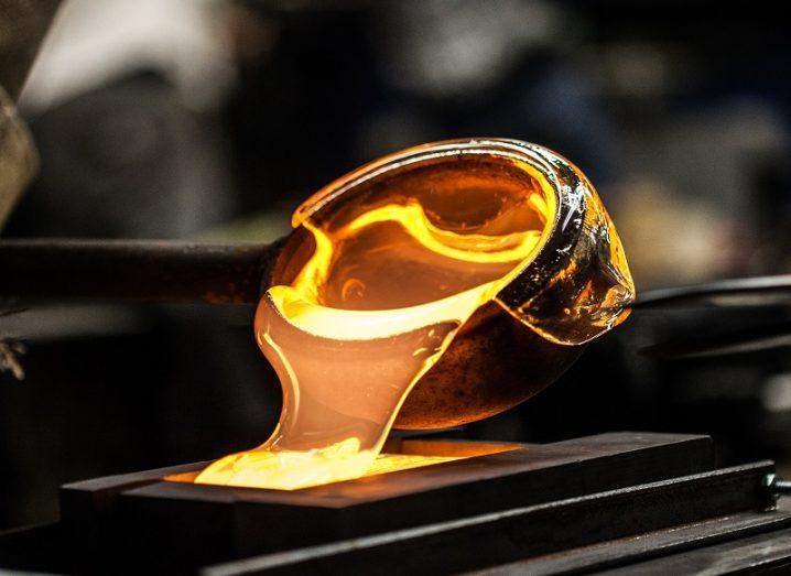 A cup of gold molten glass being poured into a mould.