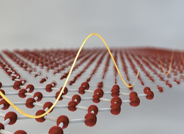 3D illustration of a sheet of red graphene atoms with a yellow wavelength running along it.