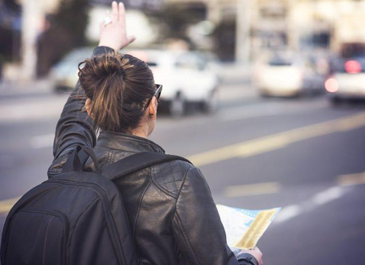 Woman with a black leather jacket and backpack trying to flag a taxi on a busy street.