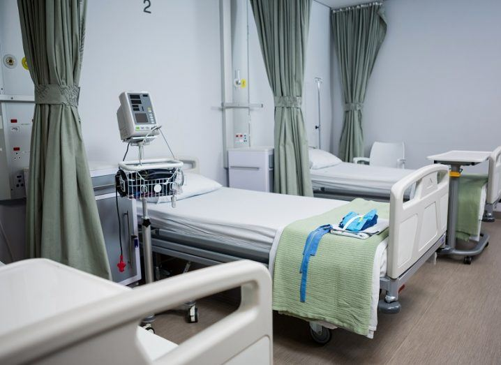 Three empty hospital beds with monitoring equipment in a white hospital room.