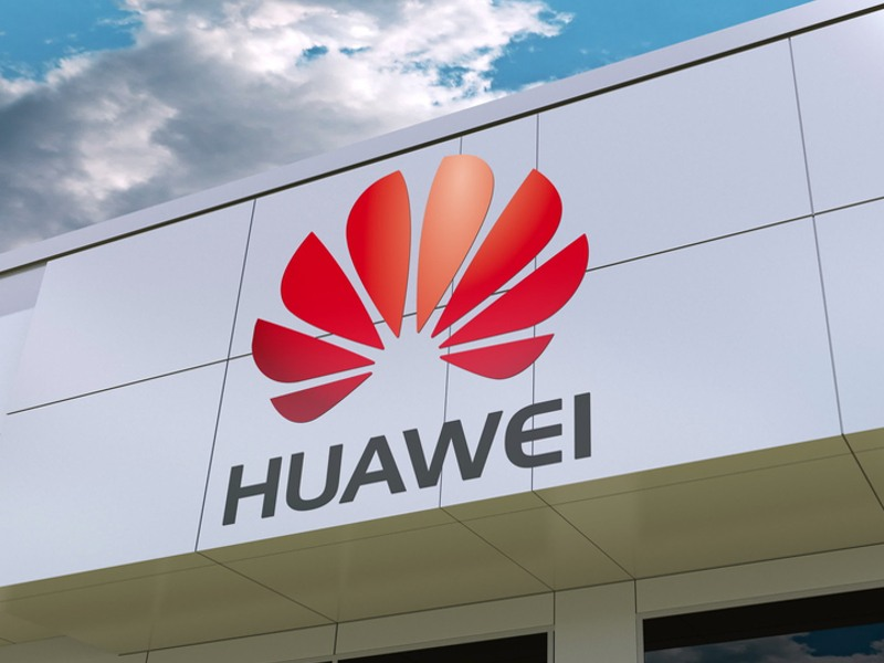 A photo of the Chinese company Huawei's logo in red on the side of a building under a blue cloudy sky.