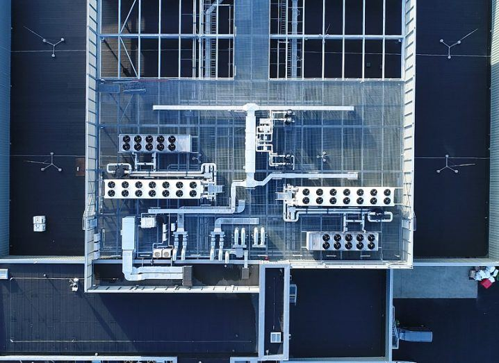 Aerial shot of a large, square building, showing rows of extractor fans and piping systems.