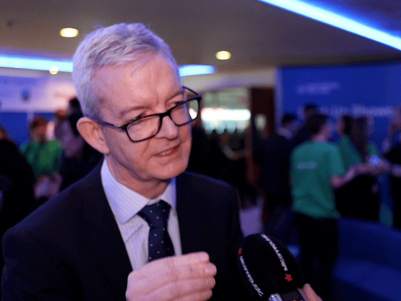 Man in business suit with grey hair and glasses arguing a point at a busy event with people in background wearing green t-shirts.
