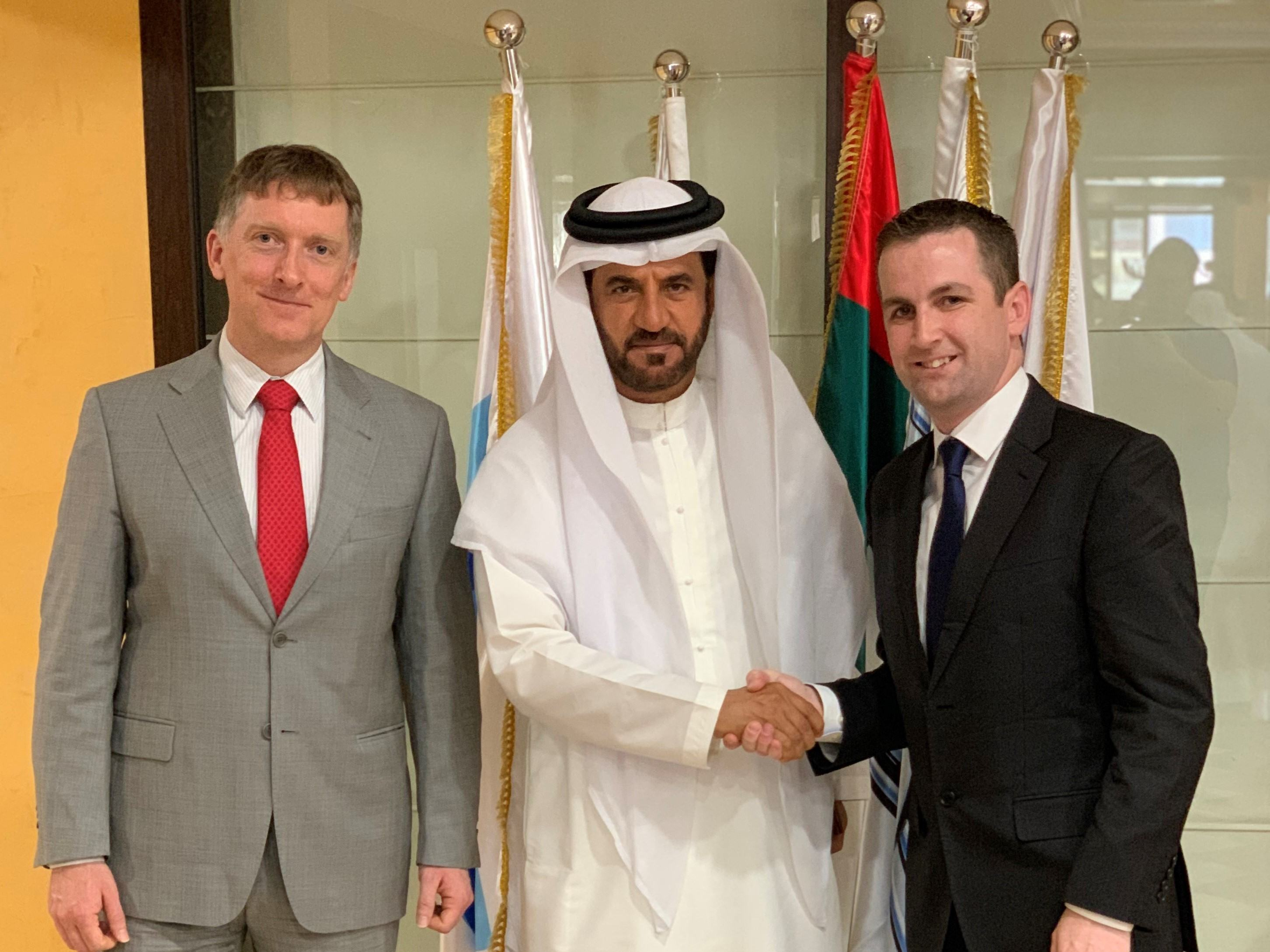 Picture of three men, one in the middle dressed in formal Arab atire, with two men on right shaking hands.