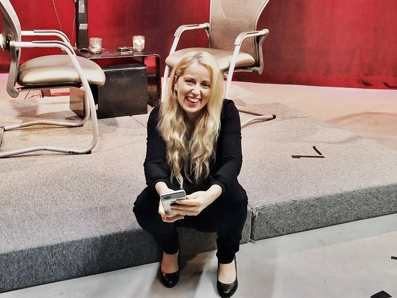 Young blonde woman smiling widely while sitting on a stage step wearing black trousers and a black top.