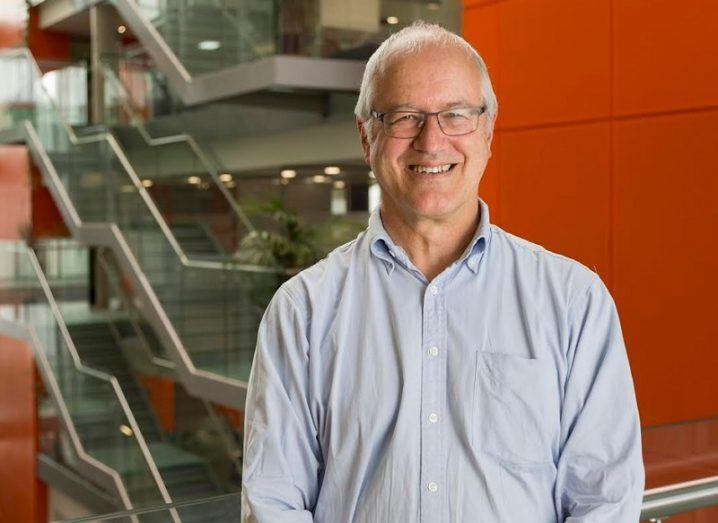 Prof Mike Benton in a light blue shirt smiling against an orange background near a tall staircase.