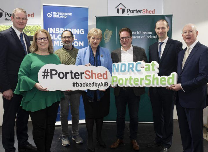 A group of people, consisting of five men and two women, hold signs denoting NDRC at PorterShed.