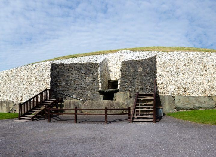 Shot outside the front entrance to the Newgrange megalithic tomb with stairs leading up to it against a blue sky background.
