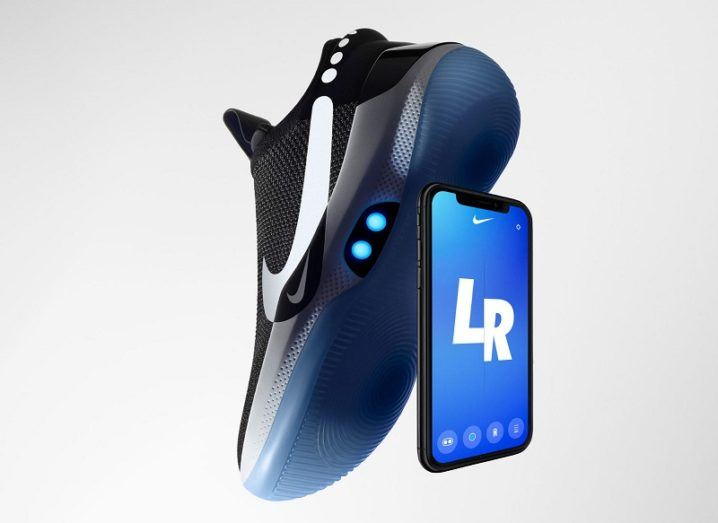 The black and blue Nike Adapt BB shoe standing vertically propped up against a smartphone with the Nike Adapt app