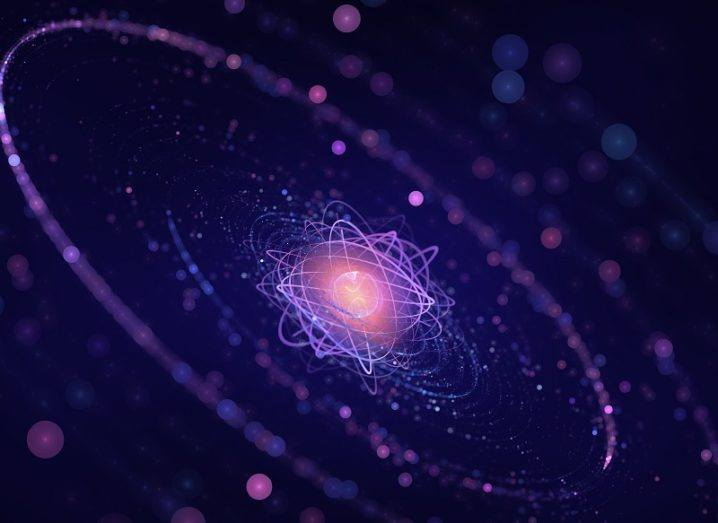 3D render of the nucleus of an atom coloured pink surrounded by purple.
