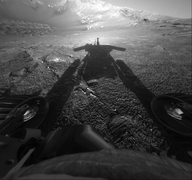 Black and white image taken by Opportunity showing its shadow against the surface of Mars.