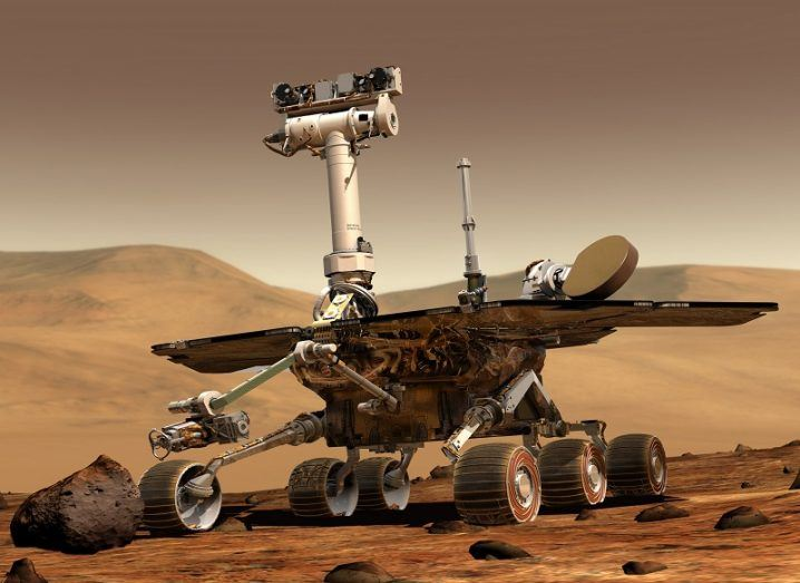 3D render of rover machine with wheels and cameras in desert-like brown surroundings of Mars.