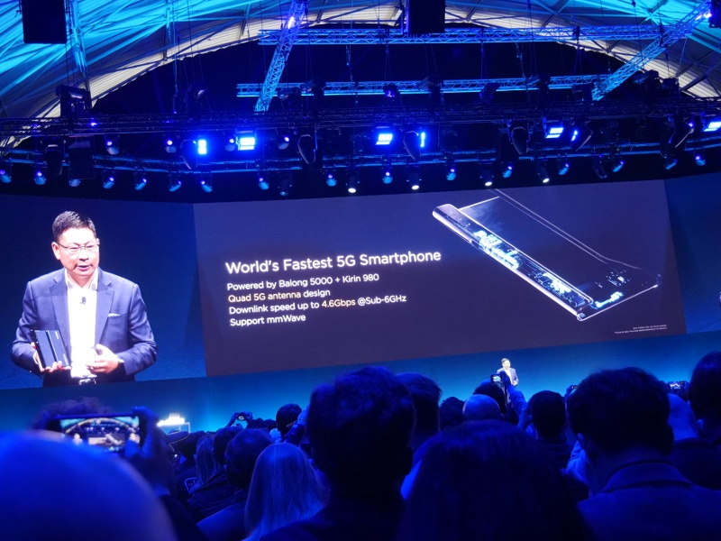 Man on stage at crowded tech event revealing specs to a new device.