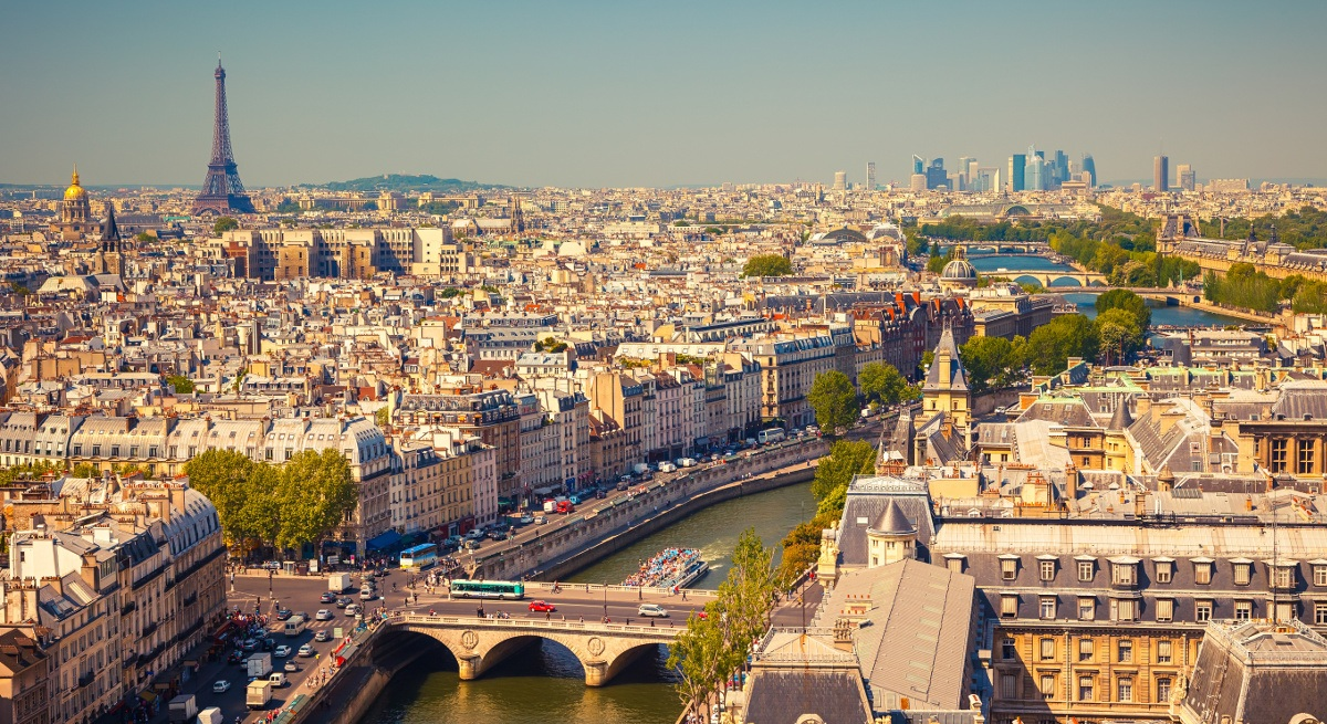 A scenic view of Paris. The River Seine runs from the foreground to the background. The Eiffel Tower is in the top left.