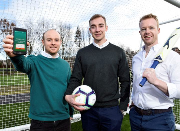 Three men standing beneath a goal net, one in a green jumper holding a smartphone while the other two hold a football and a cricket bat.