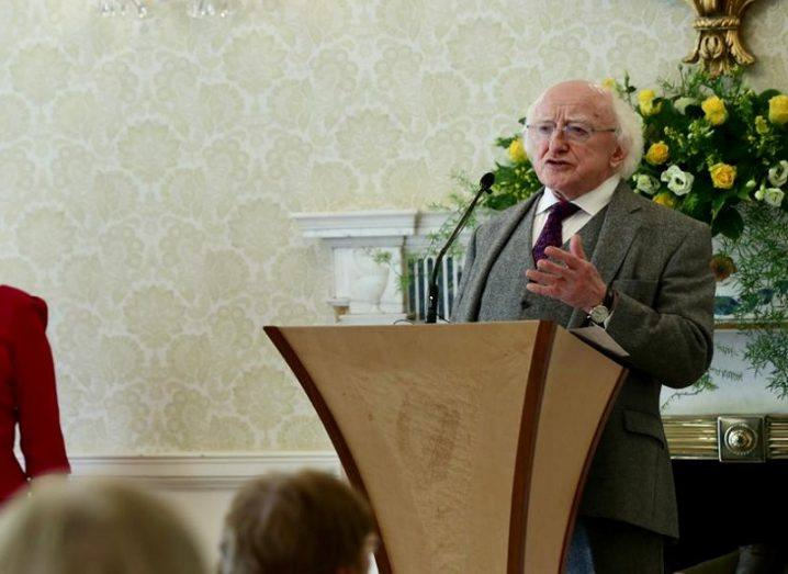 President Michael D Higgins in a grey jacket addressing people at Aras an Uachtarain from a podium in front of a fireplace.