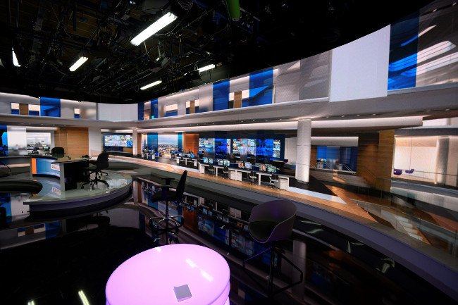 A view of the new RTE studio showing big display panels and lights with a pink neon table.